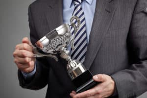 Suited man holding a silver cup