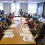 People sitting around a large table counting votes by hand