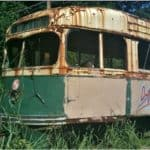 Old, rusting streetcar on a side track in the woods