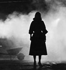 Silhouette of the back of a woman standing, gazing into fog