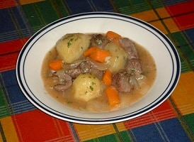 Bowl of soup with potatoes, carrots, and other ingredients
