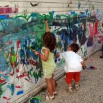 Young students painting on a wall