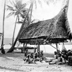 New Guinea natives in 1885 sitting on beach